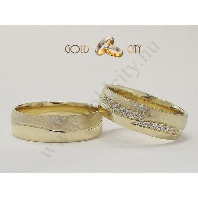 Matt és fényes, 14 karátos aranyból készült hullámos karikagyűrű a nőiben kövekkel.