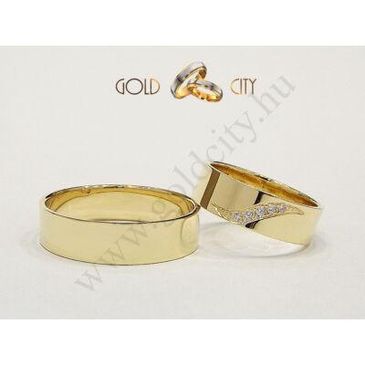 Fényes, 14 karátos sárga arany karikagyűrű, a női változat különleges foglalással kövekkel díszítve.