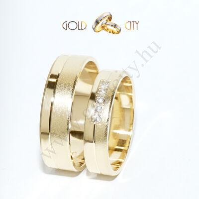 Karikagyűrű 14 karátos  sárga aranyból, a női gyűrű kövekkel díszítve.