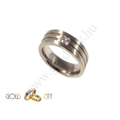 Mélyen mart, fehér arany karikagyűrű, a női változat  szögletes csiszolású kővel díszítve.