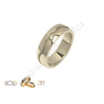 Fehér, arany karikagyűrű mélyen mart mintával.