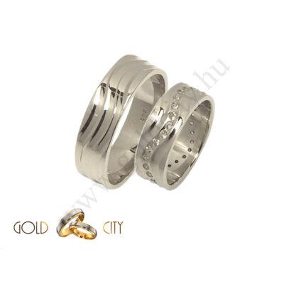 Fényes hullám mintás fehér arany karikagyűrű, a női kövekkel díszítve.
