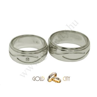 Széles, fényes, mélyen mart mintájú, fehér arany karikagyűrű, a női kővel.