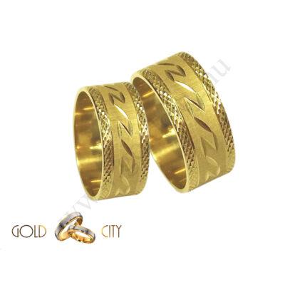 Széles, csillogó mintával díszített  14 karátos sárga arany karikagyűrű.
