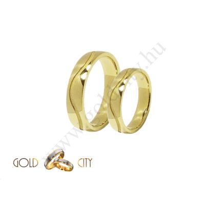 Sárga 14 karátos arany karikagyűrű, mélyen mart hullám mintával.